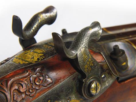 Ударная часть курков оформлена ввиде голов дракона, подстержники исполнены в виде кошачьих голов. Гравер нашел компромисс между художественным оформлением и функциональностью.